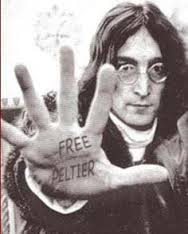 "John Lennon, palm extended with message: ""Free Leonard Peltier"""
